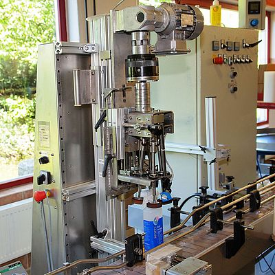 The patented capping machine from David Fuchs, www.metallatelier.de, shown here with its protective cover removed, screws on pump-spray heads