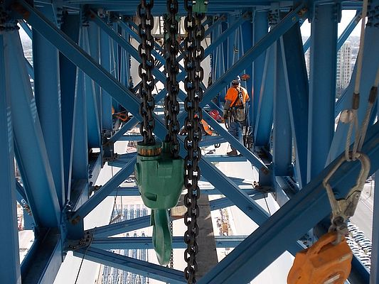 Ironworkers prepare to dismantle the 85 ton hub & spindle transfer truss, first suspending the weight of it from the newly erected chain fall platform above.